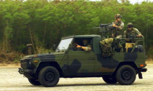 Marines from Weapons Company (WC), 2nd Battalion, 4th Marine Regiment race their Interim Fast Attack Vehicle (IFAV) along the North Field, on Tinian Island, in support of Exercise TANDEM THRUST 2003.